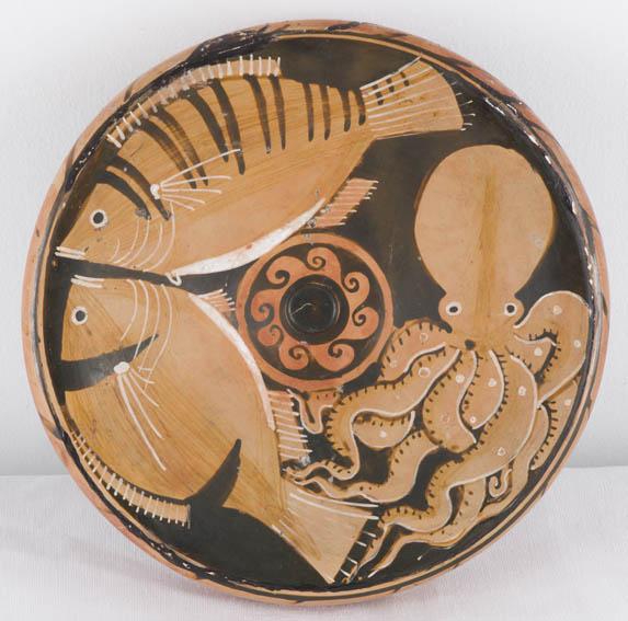 Plato de terracota realizado en el sur de Italia durante el periodo helenístico (350-300 a.C.). Figuras en color rojo decoran la pieza, las cuales representan animales marinos; una perca, una dorada y
