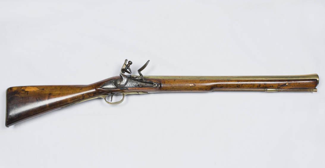 Trabuco de chispa de finales del siglo XVIII con cañón de latón. Se carga por la boca del cañón y se dispara mediante una llave de chispa. Esta arma es la predecesora de la escopeta.