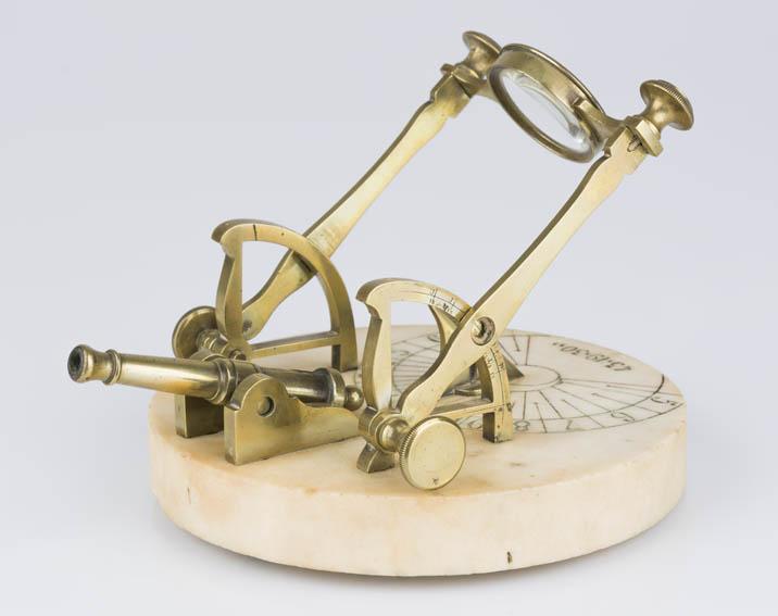 Cañón solar de bronce con un brazo articulado rematado con una lente circular de vidrio, el cual oscila para colocarlo según una marca en un lateral que corresponde con cada mes del año (solo 6 marcas