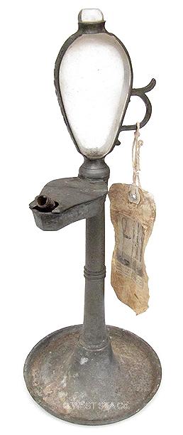 Lámpara de aceite de fabricación alemana de finales del siglo XVIII. Consta de una base y su correspondiente tronco realizados de peltre en dos piezas que se unen por rosca. En la parte superior del t